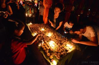 Young girl lighting candles Loy Krathong 2014