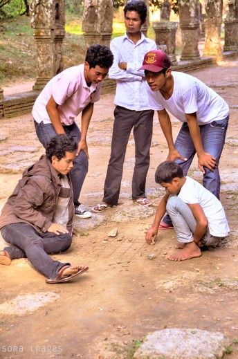 Young boys playing a game in the dirt, outside one of the temples at Angkor Wat in Cambodia